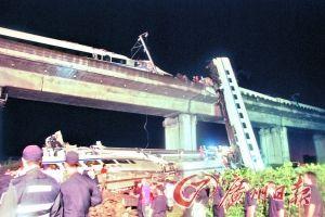 事发现场,一节车厢近乎垂直地悬挂在桥梁与地面之间。新华社发